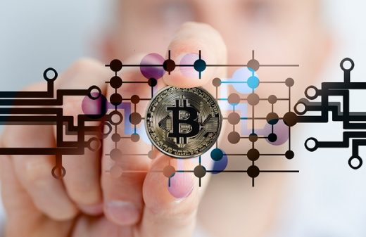 Physical bitcoin being held between finger and thumb, framed by image of computer circuitry