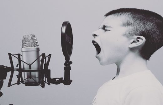 Black and white photo of a boy singing into a recording microphone, with much emotion