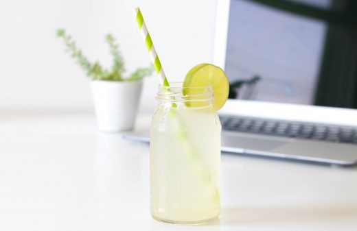 Gin in a mason jar with yellow striped straw, laptop in the background.