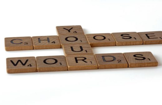 Photo by Brett Jordan on Unsplash. Wooden scrabble tiles making 'choose your words', interconnected at particular overlapping letters.