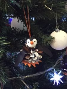 1 pine cone penguin decoration hanging from a Christmas tree branch.
