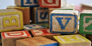 Jumble of colourful wooden letter cubes.