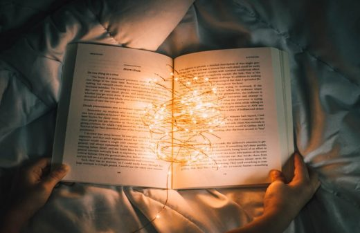 Fairy lights in the middle of an open book, resting on a duvet, in a dark room.